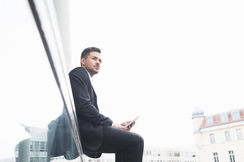 Businessman holding digital tablet while sitting on glass railing against clear sky - DIGF12184