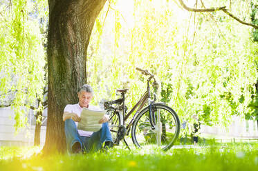 Senior man leaning against tree trunk in a park reading newspaper - DIGF12253