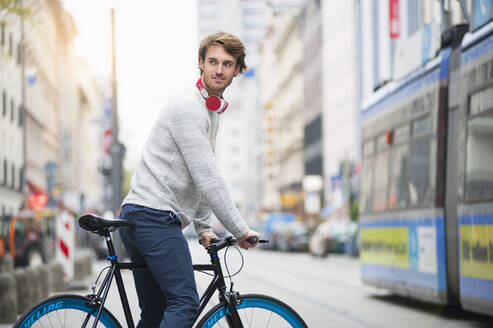 Portrait of young man with bicycle in the city - DIGF12306