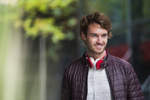 Portrait of smiling young man with headphones - DIGF12309