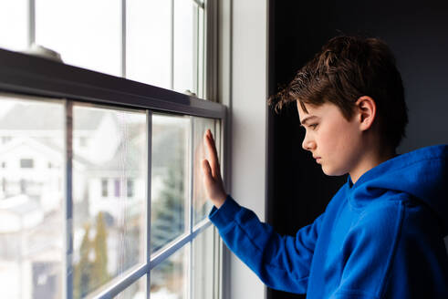 Tween boy looking out of a window in a dark room. - CAVF83056