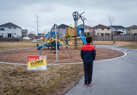 Young boy looking at closed playground during Covid 19 pandemic. - CAVF83059