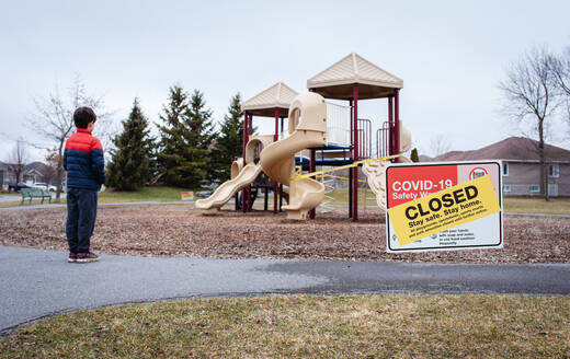 Young boy looking at closed playground during Covid 19 pandemic. - CAVF83068