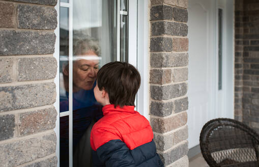 Young boy looking through window at grandma during Covid 19 pandemic. - CAVF83071