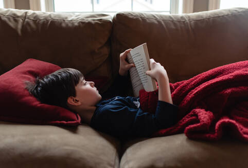 Young boy reading a book on a sofa under a blanket. - CAVF83086