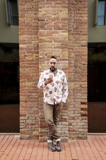 Bearded man leaning on wall while using smartphone by office building - CAVF83158