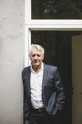 Senior businessman leaning in open office door - GUSF03808