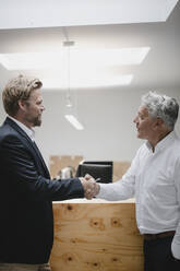 Business partners standing in office, shaking hands - GUSF03823
