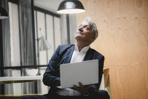 Senior businessman sitting under ceiling lamp, using laptop, looking into the light - GUSF03826