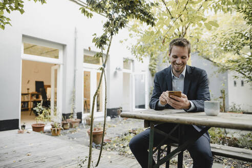 Smiling businessman sitting on bench in green backyard, using smartphone - GUSF03931