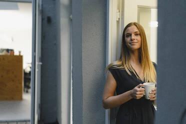 Businesswoman standing in open office door, holding cup of coffee - GUSF03955