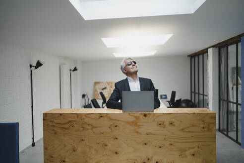 Senior businessman wearing sunglasses in office, looking up smiling - GUSF03988