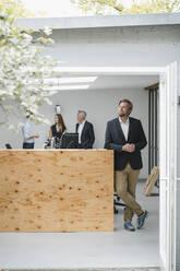 Businessman standing in open office door, people working in background - GUSF03994