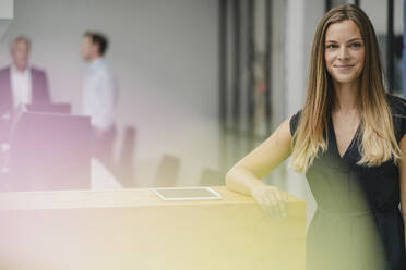 Businesswoman standing in office, leaning on wooden counter, smiling - GUSF03997