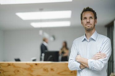 Businessman standing in open office door, with arms crossed , people working in background - GUSF04000