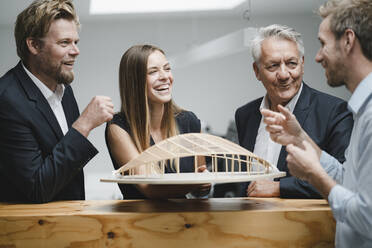 Successful business people looking at architectural model in office - GUSF04003