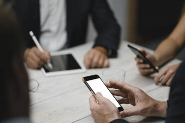 Business people working in office using portable devices, close up - GUSF04006