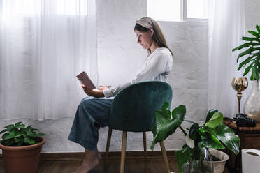 Relaxed woman reading book while sitting on chair by plants at home - ERRF03857