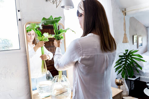 Woman holding plant while arranging in vase at home - ERRF03887