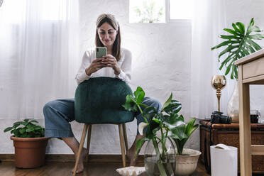 Smiling woman using smart phone while sitting on chair against wall at home - ERRF03905