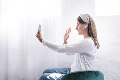 Smiling woman waving while enjoying video call through smart phone at home - ERRF03908