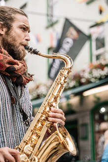 Vertical photo of a saxophonist bearded and with blonde hair playing in the street - CAVF83364