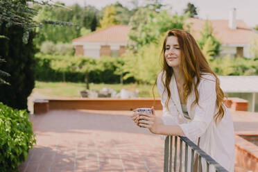 Portrait of redheaded woman with cup leaning on railing - AFVF06387
