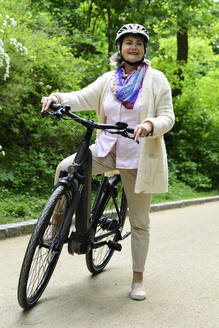 Thoughtful senior woman standing with electric bicycle on footpath in park - ECPF00931