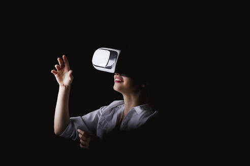 Young woman using VR glasses against black background - LJF01528