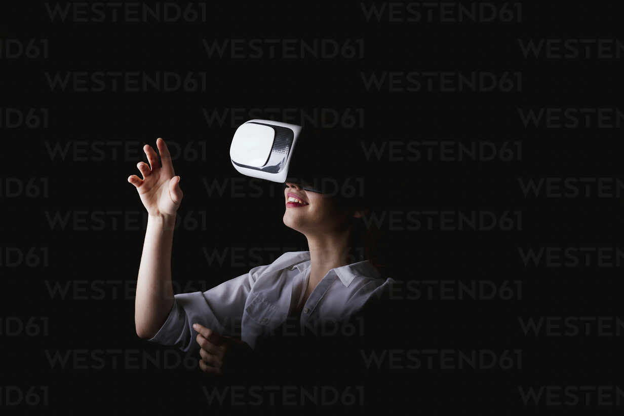 Young woman using VR glasses against black background - LJF01528 - DREAMSTOCK1982/Westend61