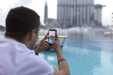 Male tourist photographing modern buildings through smart phone in Dubai, United Arab Emirates - SNF00239