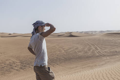 Male tourist shielding eyes while standing on sand dunes in desert at Dubai, United Arab Emirates - SNF00242
