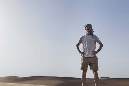 Smiling tourist standing with hands on hip against clear sky at desert in Dubai, United Arab Emirates - SNF00248