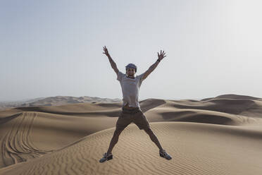 Excited male tourist jumping on sand dunes in desert at Dubai, United Arab Emirates - SNF00251