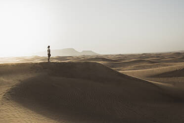 Mid distance of male tourist standing on sand dunes in desert at Dubai, United Arab Emirates - SNF00254