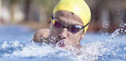 Determined male swimmer swimming in pool at tourist resort, Dubai, United Arab Emirates - SNF00257