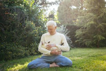 Senior man cuddling with his cat in garden - AFVF06399