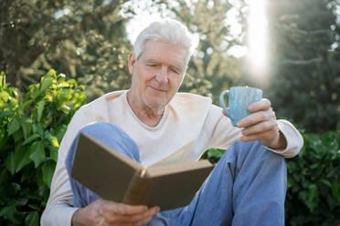 Senior man reading a book outdoors - AFVF06405