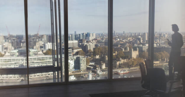 Silhouette businessman at highrise window overlooking city, London, UK - CAIF27662