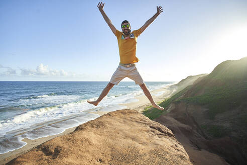 Cheerful man jumping on rock formation at beach against blue sky - VEGF02328