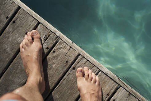 Man's feet on floorboard by swimming pool during sunny day - VEGF02331