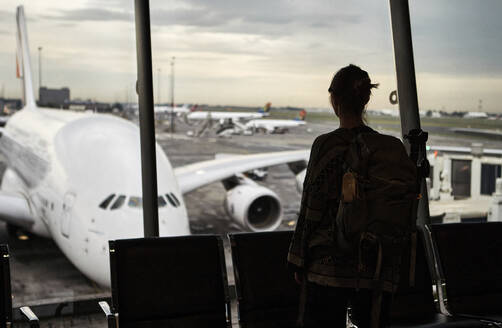 South Africa, Johannesburg, Rear view of woman looking at airplanes on tarmac from airport terminal - VEGF02340