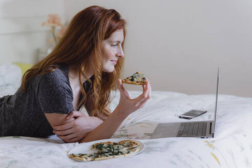 Young woman with long brown hair watching movie on laptop while enjoying pizza in bedroom - AFVF06414