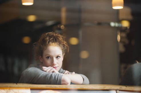 Thoughtful young woman leaning on table seen through glass window in coffee shop - DIGF12470