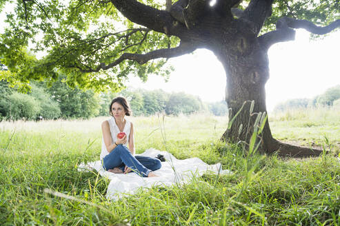 Thoughtful young woman looking away while sitting with apple on picnic blanket by tree at park - DIGF12482