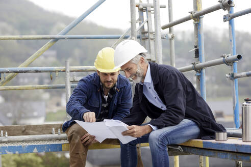 Architect and worker discussing building plan on scaffolding on a construction site - MJFKF00211