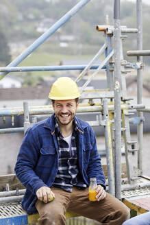 Portrait of a happy worker having a break on scaffolding on a construction site - MJFKF00217