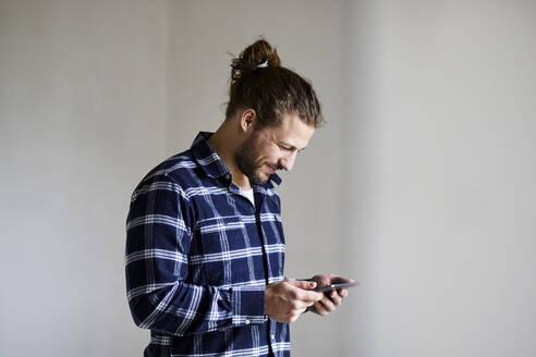 Smiling young man wearing checked shirt using smartphone - MJFKF00229