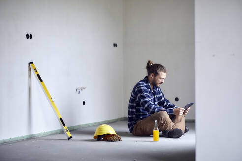 Worker on a construction site sitting on the floor using tablet - MJFKF00232