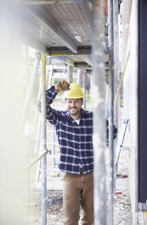 Portrait of smiling worker standing on a construction site - MJFKF00256